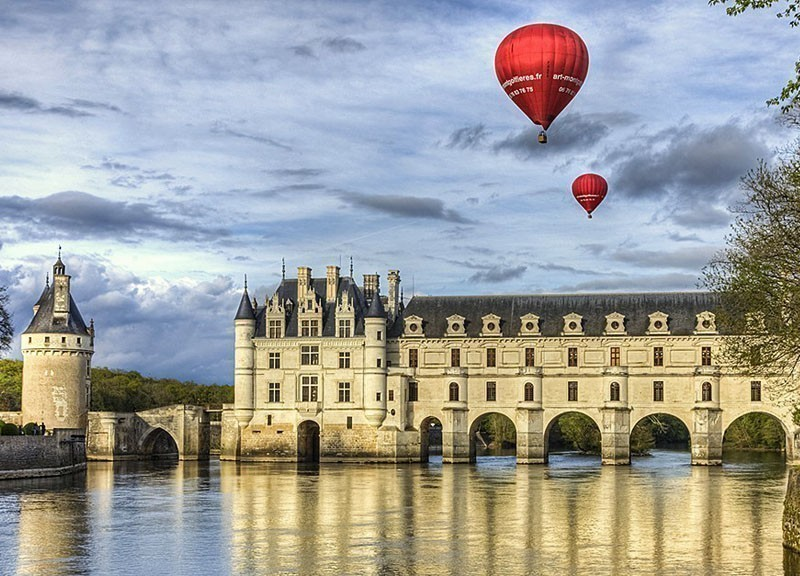Two red hot air balloons fly above the Chenonceau Castle spanning the river Cher in Chenonceaux, Loire Valley | 10 Best Hot Air Balloon Rides Around The World