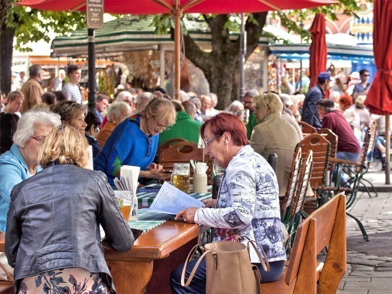 People eating bavarian lunch in Viktualienmarkt, a gourmet market and touristic attraction in Munich, Germany | What to Do in Munich in 3 Days