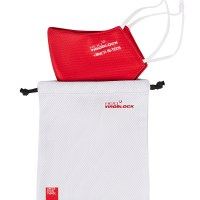 Photograph of the HeiQ Viroblock Protective Washable Mask Bag. The text HeiQ Viroblock + Multi Hi-Tech is written on the top right corner of the bag, and there is a tag which says Swiss Tech Inside is on the bottom left of the bag. The bag fits two masks. Image shows two hands putting a red mask in the mask bag for illustrative purposes only.