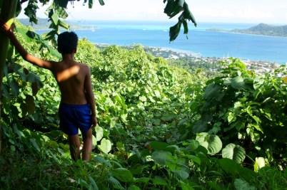 A boy looks out to sea in Bora Bora