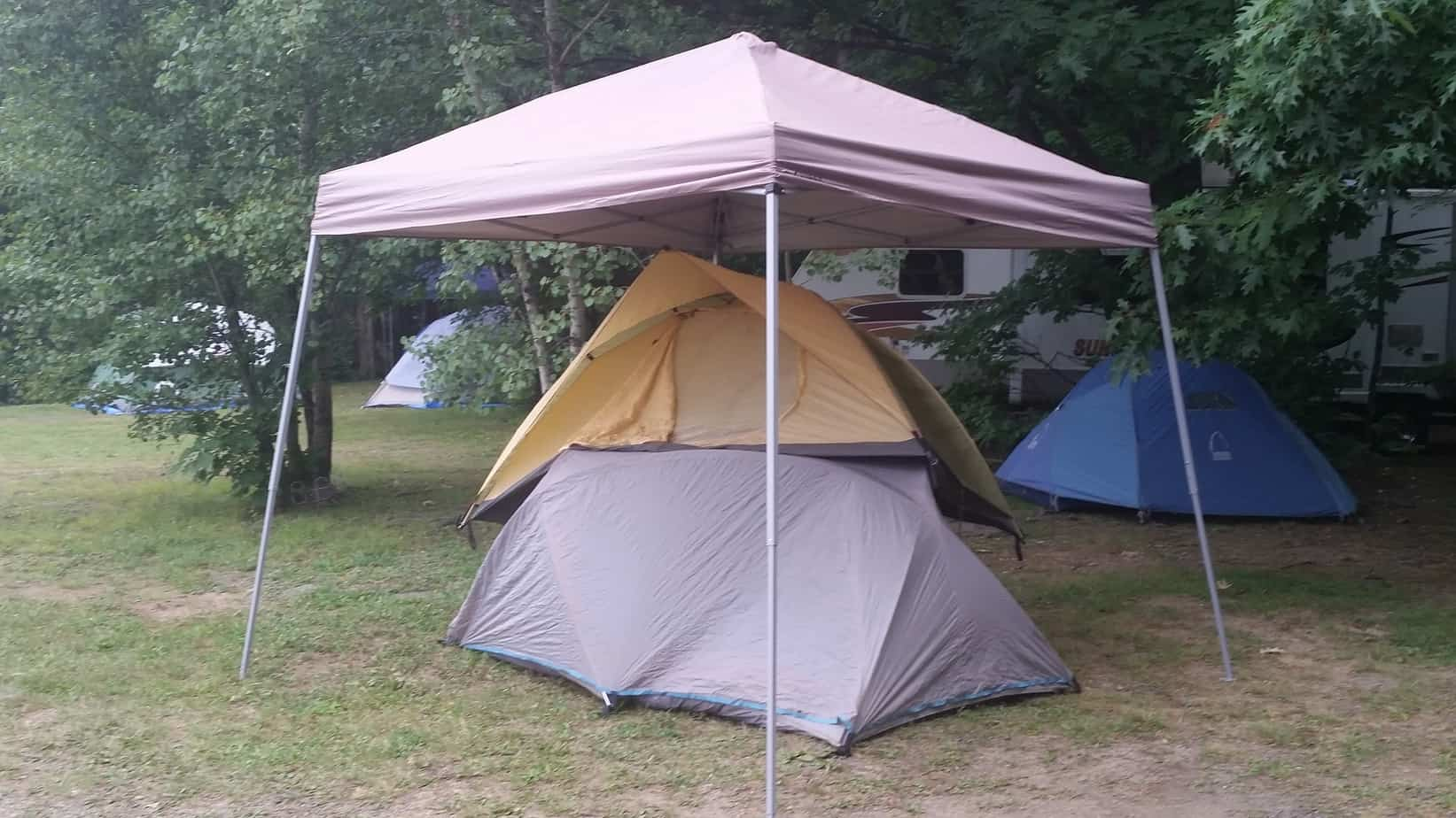 Pile of tents under a popup canopy & How To Stay Dry While Camping   Must Go Camping