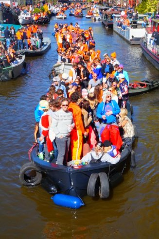 Longboat cruising Amsterdam on Kings Day