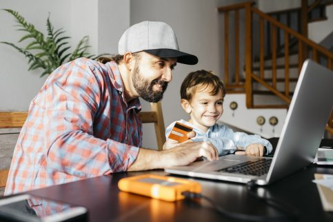 Father and son using laptop together, online shopping