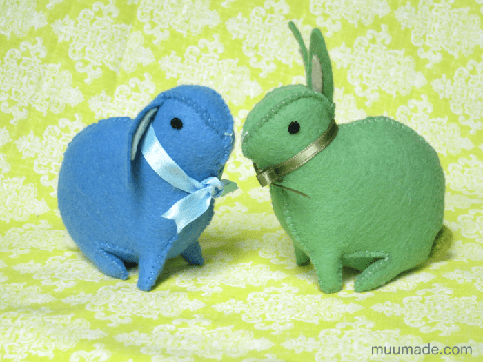 A green bunny and a blue floppy eared bunny looking at each other