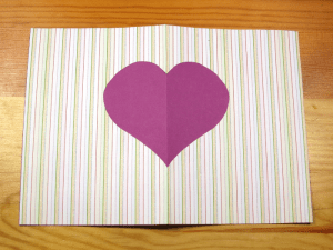 Paper cut out card with a purple heart in the middle