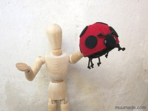 Lucky Ladybug Finger Puppet on a wooden mannequin