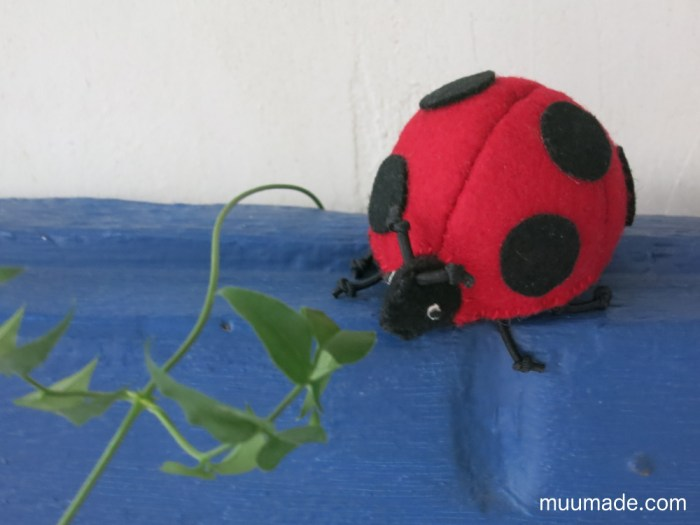 Lucky Ladybug Finger Puppet on a blue wooden pane
