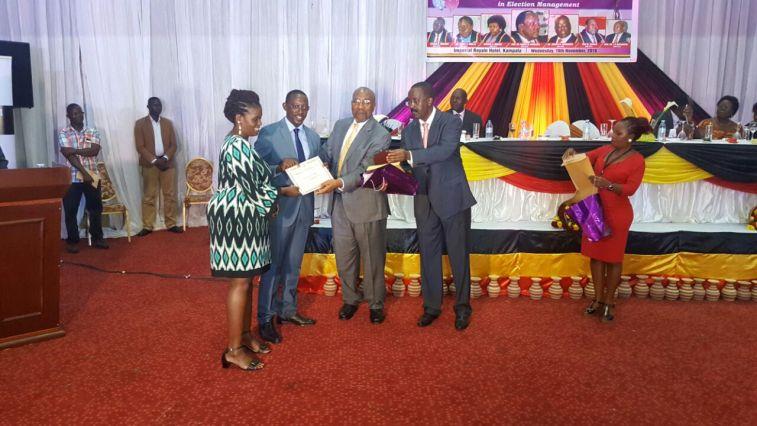 Kosiya receiving an award from Hon Ruhakana Rugunda