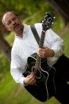 Stan Stewart plays guitar and sings
