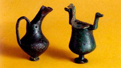 Бронзени висулци -минијатурни грниња, еден со капак и симболични додатоци во облик на птичји глави. Се обесувале на појасот на покојникот и го симболизирале ослободувањето на душата (птица) после смртта од телото (грне).