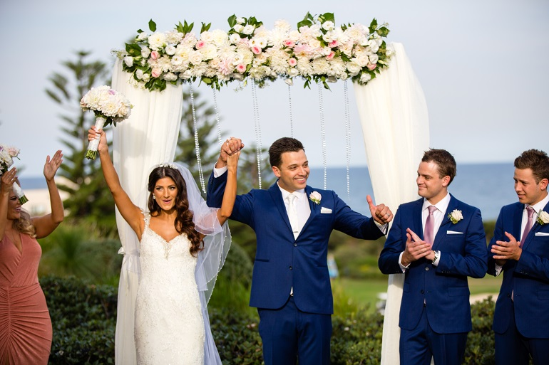 Wedding Ceremony Venue with Floral Ceremony Arch and Beach Views