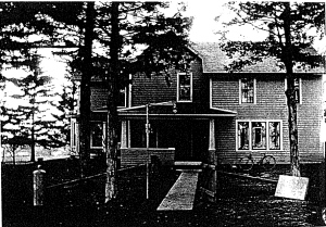 Black and white photo of a farmhouse from the front.