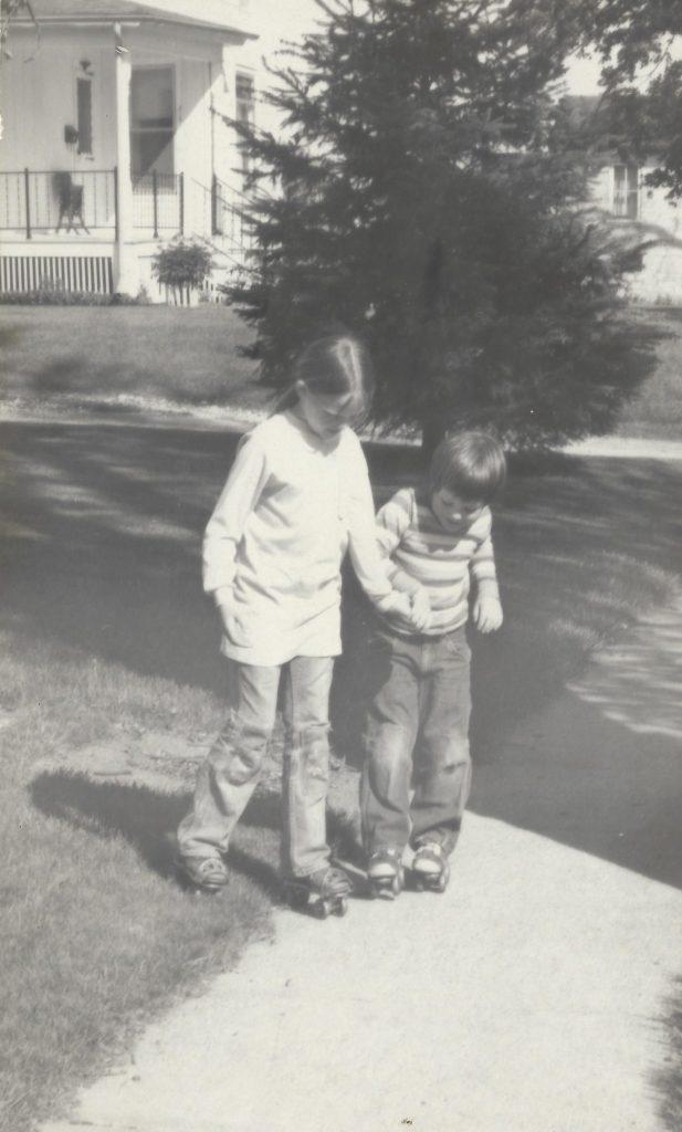 Photo of Kirsten Sutherland teaching her brother Warren how to skate. 1975