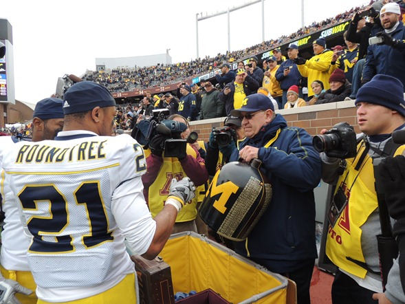 Jon Falk delivers the Little Brown Jug to Michigan players