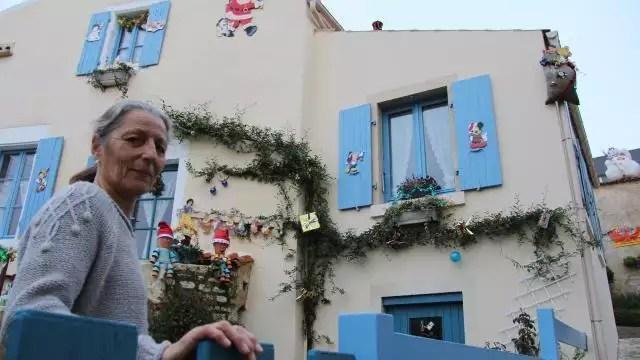 photo brigitte devant la facade de sa maison sur laquelle trone le pere noel