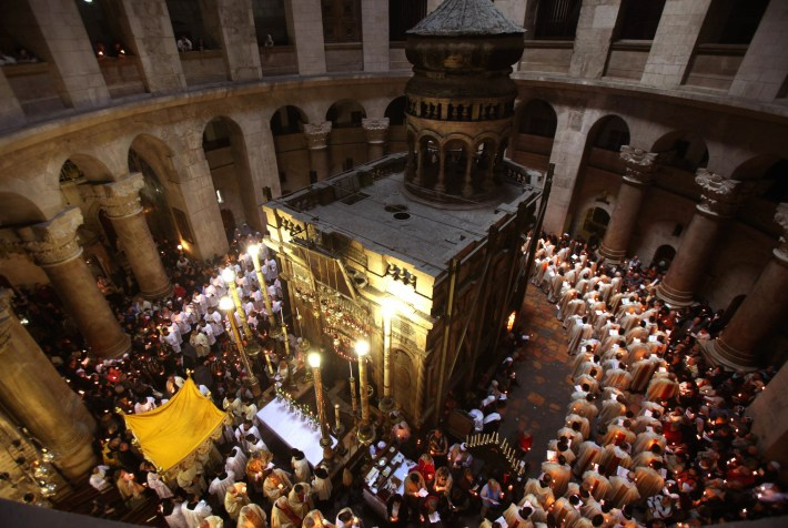Roman Catholic clergy men hold candles as they circle the aedicule during the Holy Thursday Easter procession at the Church of the Holy Sepulchre in Jerusalem's Old City on April 09, 2009. Christian believers around the world mark the solemn period of Easter in celebration of the crucifixion and resurrection of Jesus Christ. Christians traditionally believe the church is built on the site where Jesus was crucified and buried. AFP PHOTO/GALI TIBBON (Photo credit should read GALI TIBBON/AFP/Getty Images)