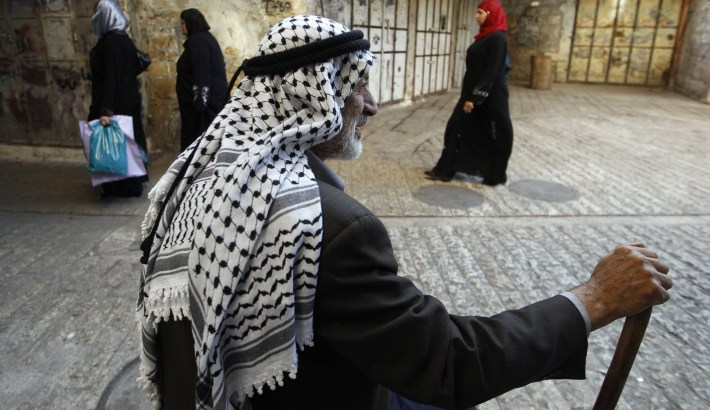 A Palestinian man wears a keffiya headdress in the West Bank city of Hebron