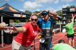 Mike Vulanich, center, of San Francisco, waits to get a bottle of water after finishing the Ironman 70.3 Ohio triathlon on Sunday, August 21, 2016 at Selby Stadium in Delaware, Ohio. Vulanich finished a 1.2-mile swim, a 56-mile bike ride and a 13.1-mile run in 4 hours, 12 minutes and 53 seconds for first overall. (Joshua A. Bickel/ThisWeek Community News)