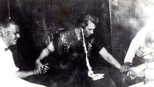 """Margery"" expels ""ectoplasm"" during a seance."