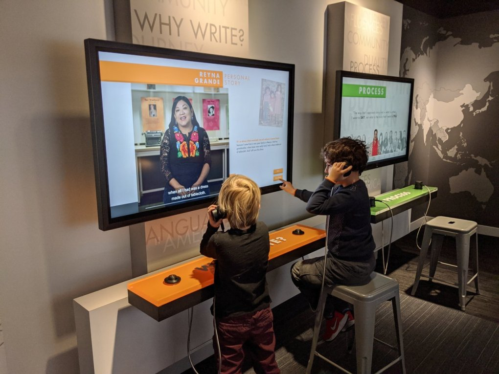 "Two young students engage with the ""Why Write?"" monitor in the My America: Immigrant and Refugee Writers Today exhibit at the American Writers Museum in Chicago"