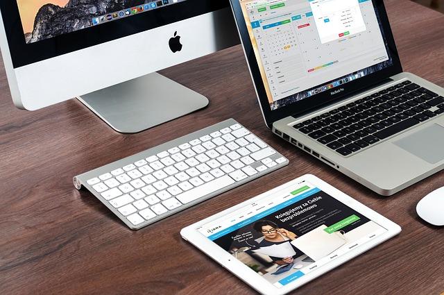 Sur un bureau il y a un Imac, un MacBook Pro et un IPad