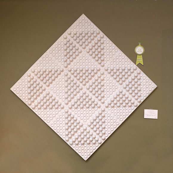Booth #118, Deluxe Inc.: A white diamond wall hanging.