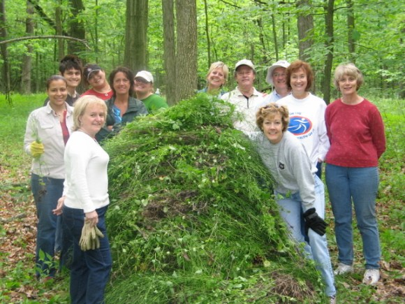 """Garden volunteers pose with a pile of removed garlic mustard at an annual """"garlic mustard pull"""" event."""
