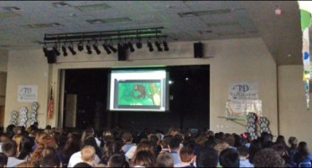 PHOTO: An auditorium of kids watches our broadcast on a projection screen on stage.