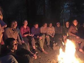 PHOTO: the scholars in the program are sitting around a campfire at night.