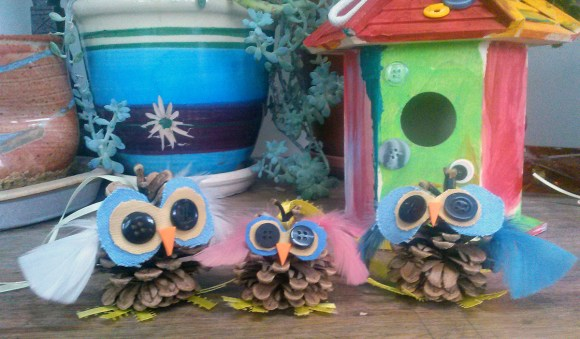 PHOTO: A family of hand-made pinecone owls using buttons for eyes and ribbon feet.