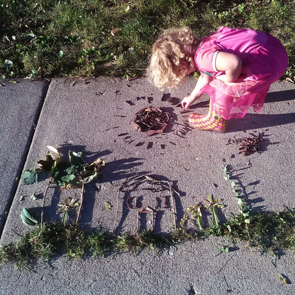 PHOTO: Sticks and grass make a portrait of our house; Laila works on a mulch sun.