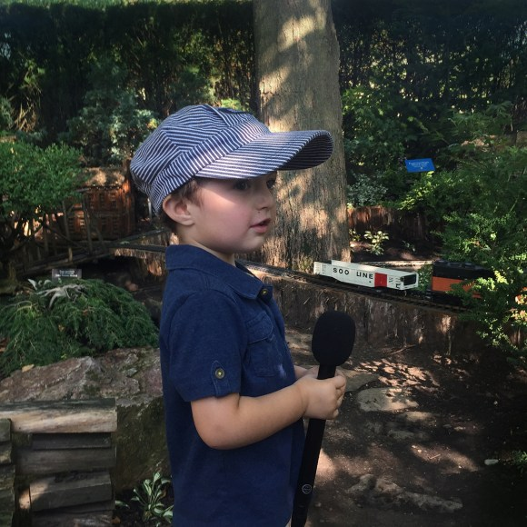Small boy with a microphone talks about the Model Railroad Garden.