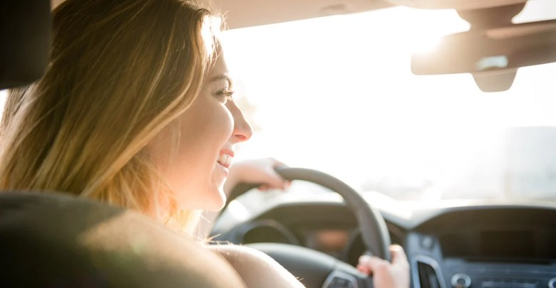 girl driving in car with a smile and sunshine coming through the window