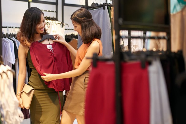 Two women shopping in a store, deciding which clothes to buy
