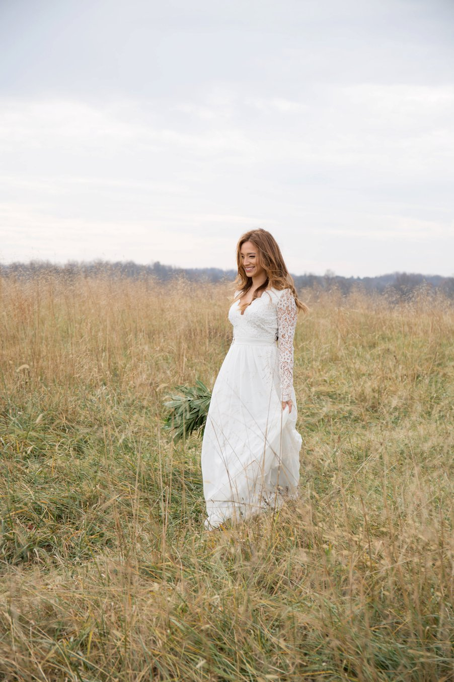 bride smiling and walking through field