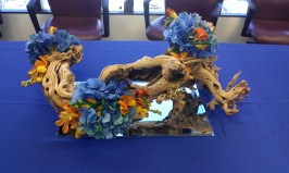 Driftwood dotted with flowers. The blue is the same as the logo.