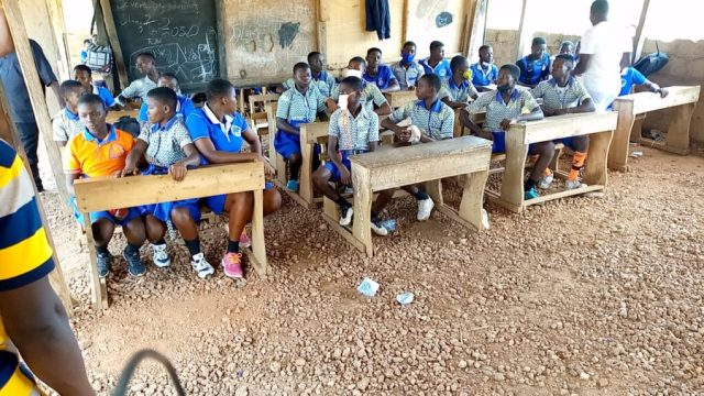 Students of Duadaso No.2 SDA JHS sitting in an open classroom structure with an uncemented floor