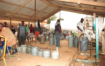 people at a gas station to fill gas cylinder