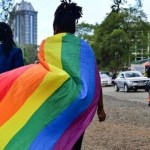 A lady covers her back with the LGBTQI+ flag