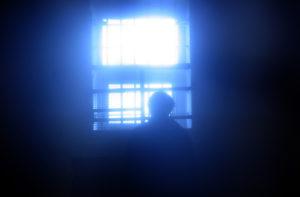 Man in Prison Looking Out Window