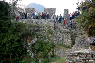 Trekkers arriving to the Sun Gate and seeing Machu Picchu for the first time.