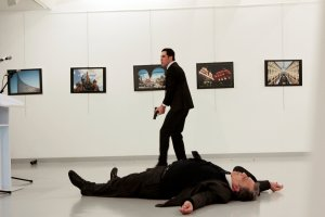 A man, reported by The Associated Press to be the gunman, after the shooting of the Russian ambassador, on the floor, on Monday at a gallery in Ankara, the capital of Turkey. Credit Hasim Kilic/Hurriyet, via Reuters