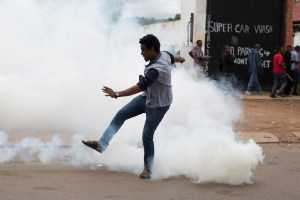 A man reacts to tear gas fired by police to disperse protesters in Pretoria on Feb. 24. Mobs have looted stores believed to belong to immigrants. (James Oatway/Reuters)