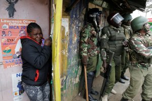 A woman sought cover Saturday as Kenyan police officers clashed with supporters of the opposition leader Raila Odinga in the Kibera neighborhood of Nairobi, the capital.  Credit Goran Tomasevic/Reuters