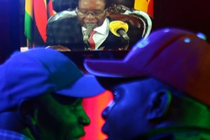 People watch as Zimbabwean President, Robert Mugabe addresses the nation on national television, at a bar in Harare