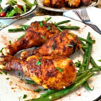 Plate of drumsticks made in an air fryer, with grean beans.