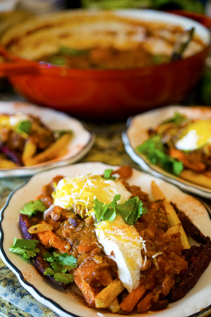 Three dishes of vegetarian chili topped with sour cream and shredded cheese.