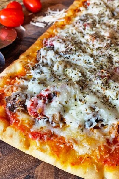 Flatbread pizza with cheese and oregano on top.