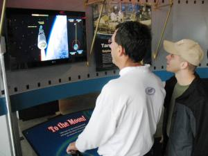 A couple of visitors try their hand at steering a Saturn rocket through space.