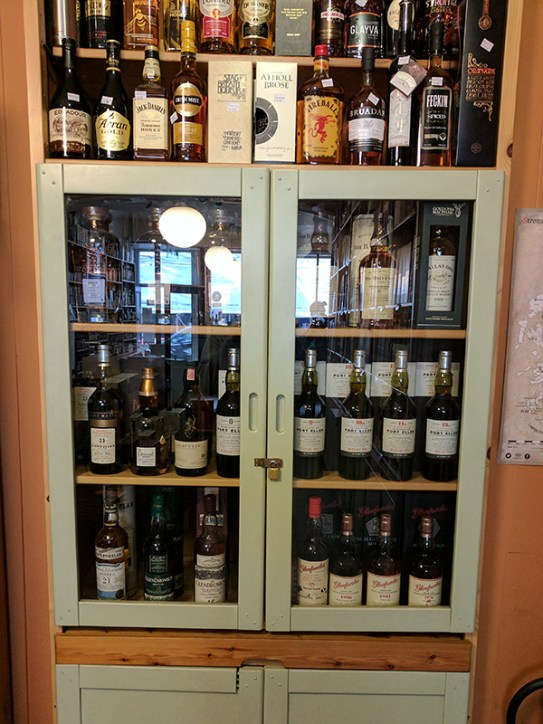 One of the cabinets with high-end bottles.